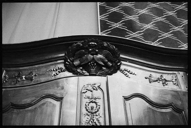 photographie - Hôtel Drouot. Médaillon sur le fronton d'une armoire probablement normande, en noyer, décoré de deux tourterelles dans une couronne de feuillages