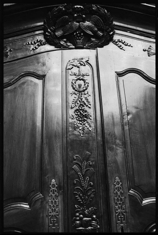 photographie - Hôtel Drouot. Vue en détail du fronton jusqu'à la serrure centrale d'une armoire probablement normande, en noyer