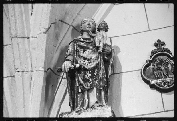 photographie - Statue de la Vierge en pierre polychrome. A côté, un médaillon représentant Jésus à la Cinquième Station, un Cyrénéen l'aide à porter sa croix