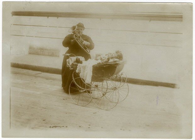 photographie - Le 14 juillet à Paris. Pour soulager sa misère, une pauvre mère poussant dans une petite voiture une petite fille infirme, implore la pitié des promeneurs en jouant de la basse