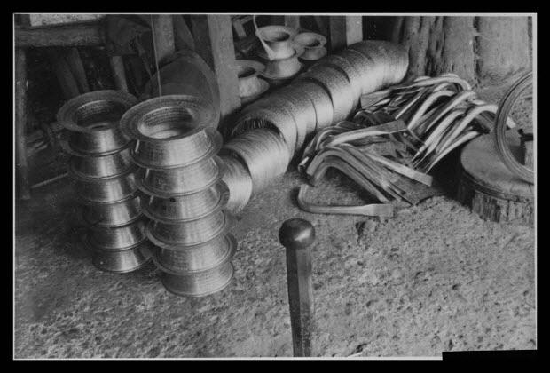 """photographie - Chez Monsieur Roblin, chaudronnier. Pièces de canne pour ceux qui font le """"charabis"""" (la réparation). De gauche à droite : cols, pieds, anses et cordons"""