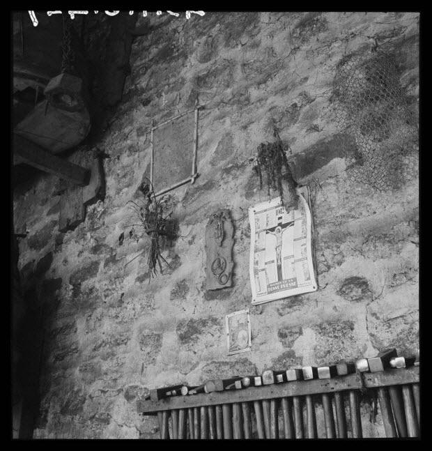 photographie - Chez Monsieur Roblin, chaudronnier. Râtelier au marteau, image et bouquet et figurine de saint Hubert en plomb