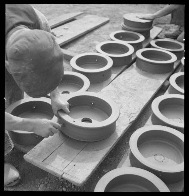 photographie - Entreprise de poterie Plaisance. Un manœuvre perfore des enfourneurs