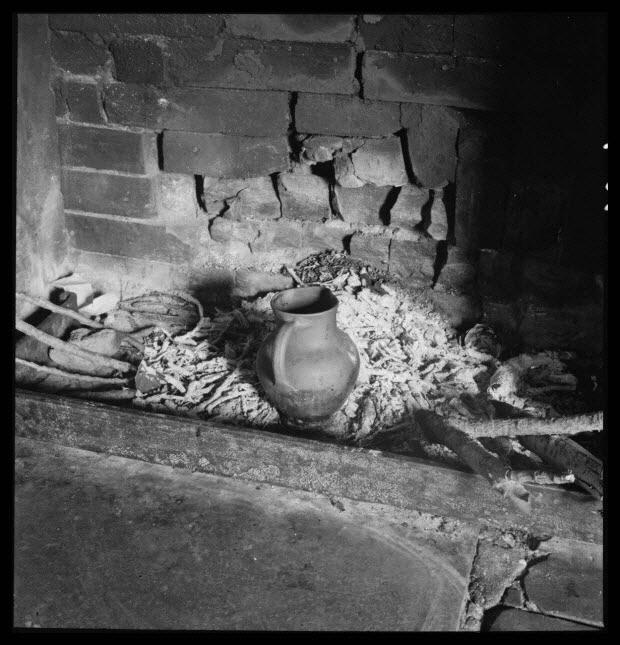 photographie - Chez Monsieur Désiré Lefrançois, maire. Petit pot à café gobin en grès de Noron, chauffant dans la cendre de l'âtre. En avant, barre de foyer