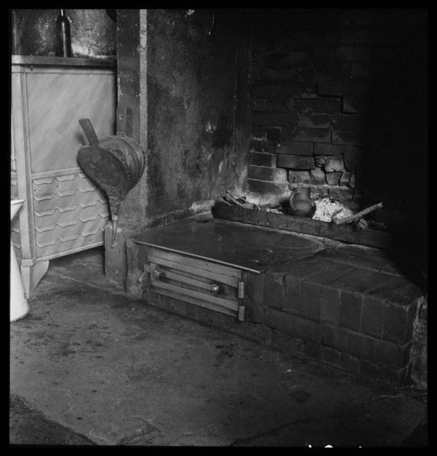 photographie - Chez Monsieur Désiré Lefrançois, maire. Dans l'âtre, petit pot à café de Noron en grès chauffant dans la cendre. Barre de foyer et soufflet de Sourdeval. Le four Est une...