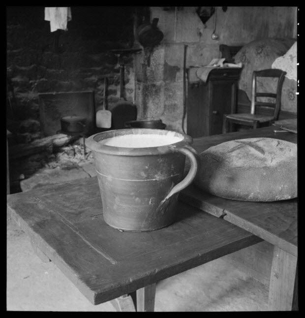 photographie - Chez Madame Veuve Louis Hérard. Pot à crème en grès de Ger, table à tirette, miches de pain marquées d'une croix. Dans l'âtre, une tuile et une palette à galettes