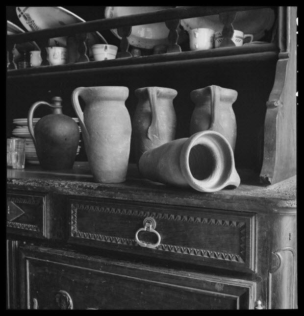 photographie - Chez Madame Veuve Louis Hérard. Sur le vaisselier, poterie en grès de Ger. De gauche à droite : une bouteille à goutte et quatre chanettes à miel