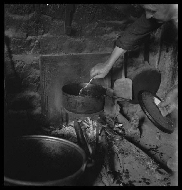 photographie - Chez Madame Veuve Louis Hérard. Madame Paillette surveille la cuisson d'une fricassée de lapin dans une casserole en fonte, posée sur un trépied. Dans le fond de l'âtre : une...