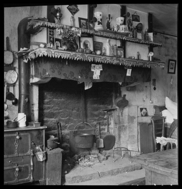 photographie - Chez Madame Veuve Louis Hérard. Vue générale de l'âtre et de la hotte de cheminée. Dans l'âtre, un chaudron de cuivre pendu à la crémaillère, une tuile à galettes, une palette...