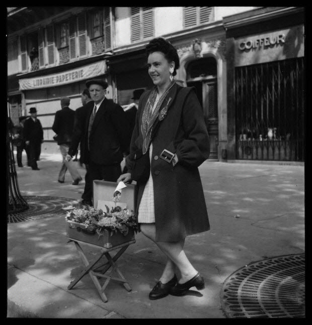 photographie - 18, boulevard Beaumarchais. Défilé du 1er mai 1946, fête du travail. De 14 heures à 19 heures. Vendeuse de muguet. Mademoiselle Janssen, venue de la région de Senlis, sans métier...