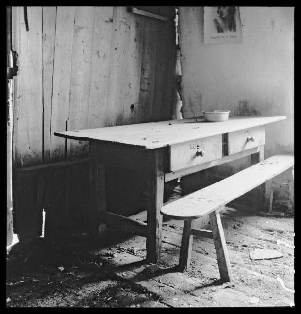photographie - Maison Gonnet. Salle commune, cloison de bois séparant la salle de l'étable, table à deux tiroirs et banc