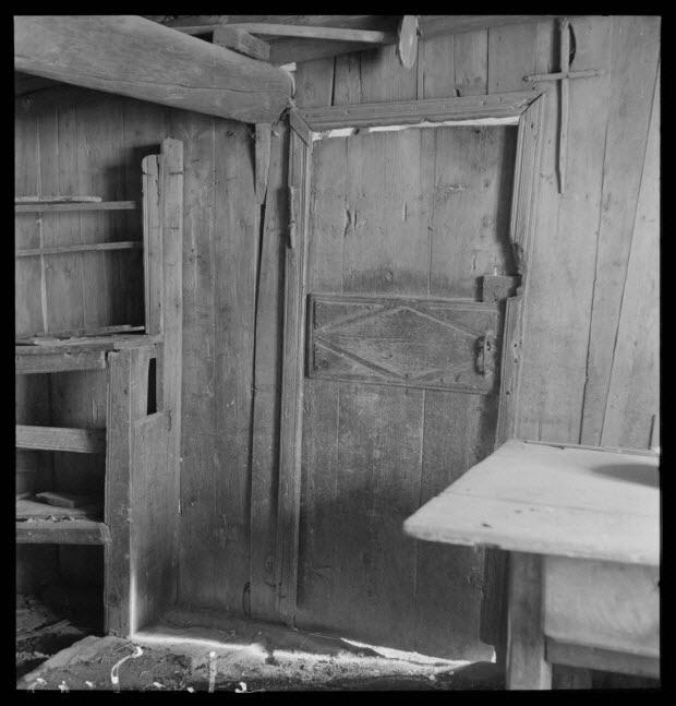 photographie - Maison Gonnet. Salle commune avec cloison de bois et porte donnant sur l'étable et angle du vaisselier