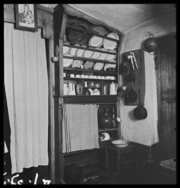 photographie - Maison P. Faure. Salle commune : vaisselier, porte donnant sur le corridor et rideau masquant l'alcôve