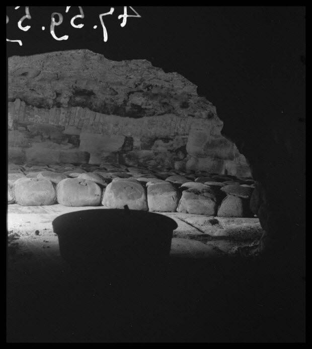 photographie - Bourg. Fournil. Tourtes disposées dans le four après la cuisson. Au premier plan, la marmite en fonte contenant la tourte de choux