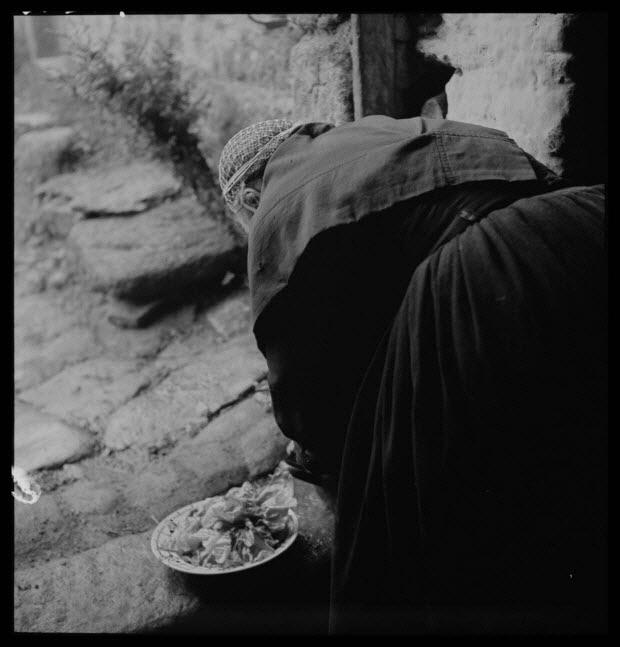 photographie - Mademoiselle Jeanne-Marie Panhaleux lavant une salade dans un récipient en métal sur le seuil de la salle commune