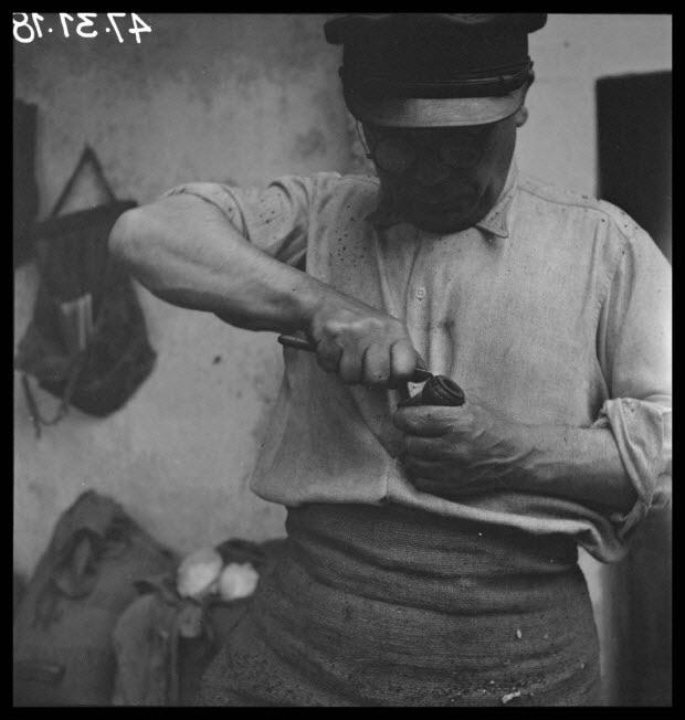 photographie - Monsieur Yann Douirin incise une pièce du biniou au couteau
