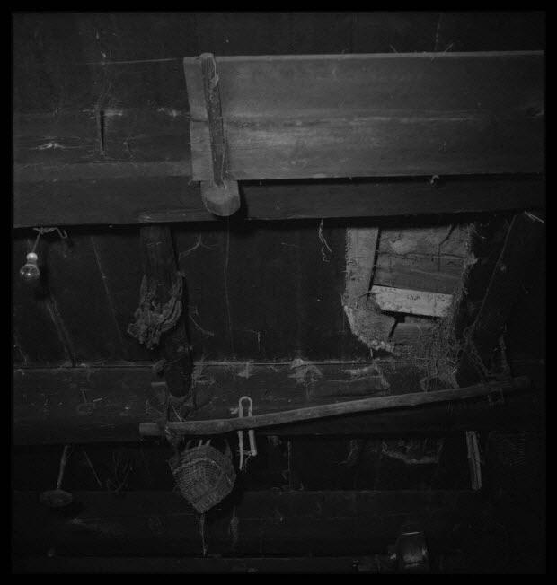photographie - Chez Monsieur Raymond Gendraud. Salle commune. Dispositif pour accrocher le porc au plafond. Vue prise de l'âtre de la cheminée