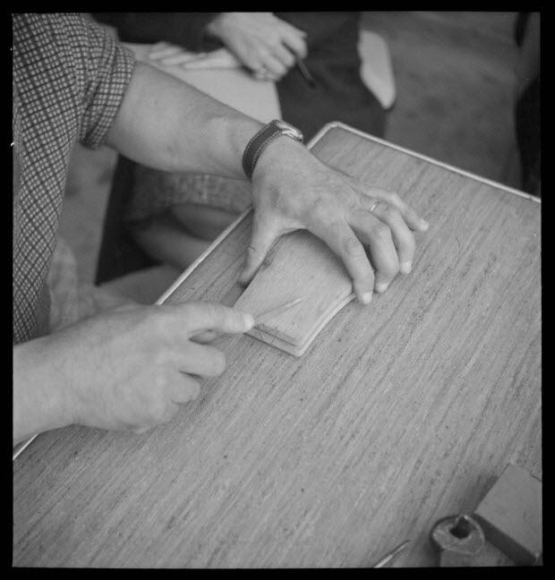 photographie - Chez Monsieur François Delabre. Fabrication d'un soufflet de cabrette : polissage des têtes de vis à la lime