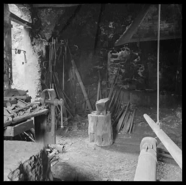 photographie - Chez Monsieur Marius Maria. Angle Sud-Ouest de l'atelier avec porte d'entrée, établi, forge et tête de marteau