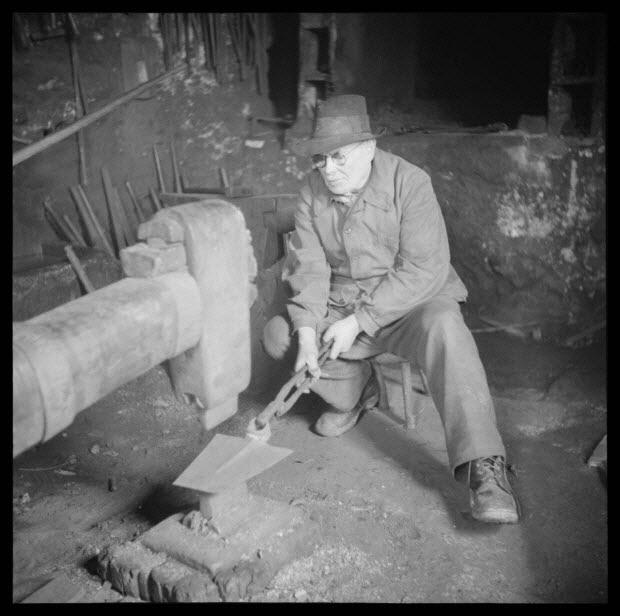 photographie - Chez Monsieur Bernard Bracco. Tête du marteau du martinet et Monsieur Bracco au travail