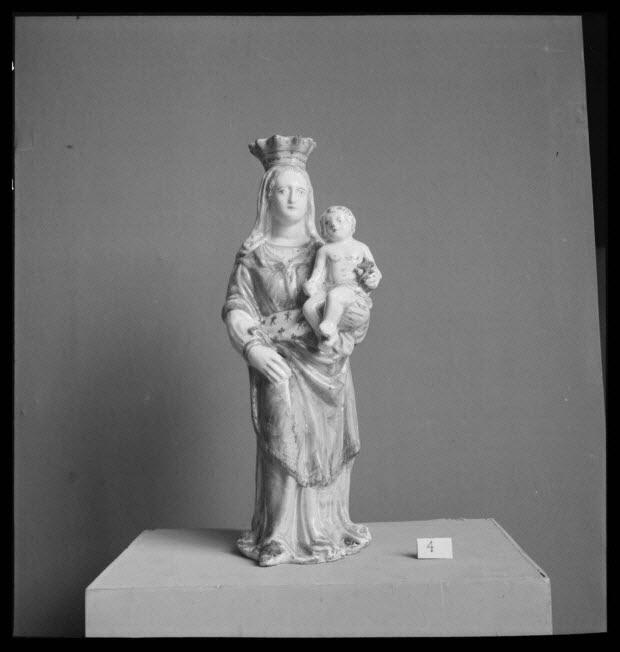 photographie - Statue de Nevers. Vierge couronnée qui présente l'enfant Jésus sur le bras gauche. Celui-ci tient une sphère surmontée d'une croix (dépôt du Musée de la céramique)